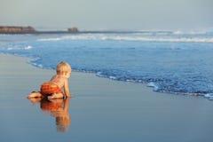 在日落沙子爬行到游泳的海的海滩婴孩 免版税库存图片
