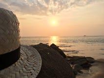 在日落海景的帽子 图库摄影