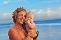 在日落海海滩的愉快的家庭-生举行小儿子 库存图片
