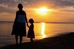 在日落海滩的母亲和孩子剪影 免版税库存照片