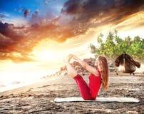 在日落海滩的瑜伽 库存图片
