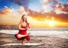 在日落海滩的瑜伽 免版税库存图片