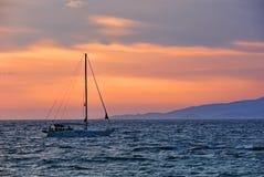 在日落海的小船 免版税库存照片