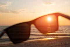 在日落海背景的太阳镜 免版税库存照片