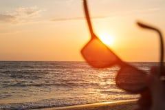 在日落海背景的太阳镜 免版税图库摄影