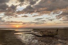 在日落海滩搁浅的老木水手小船 库存照片
