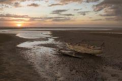 在日落海滩搁浅的老木水手小船 库存图片