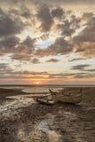 在日落海滩搁浅的老木水手小船 免版税库存照片