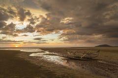 在日落海滩搁浅的老木水手小船 免版税图库摄影