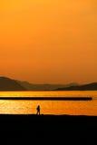 在日落海滩的人步行 免版税库存照片