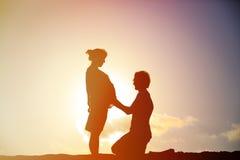 在日落海滩的愉快的怀孕的夫妇 免版税库存照片