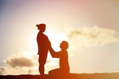 在日落海滩的愉快的怀孕的夫妇 免版税库存图片