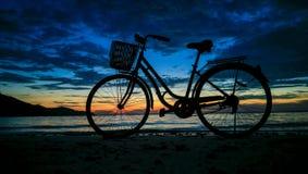 在日落海滩的自行车 免版税库存照片
