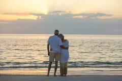 在日落热带海滩的资深夫妇 免版税库存照片