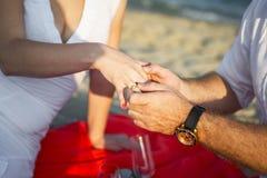 在日落热带海滩的结婚提议 库存照片