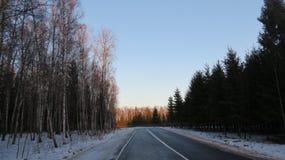 在日落的一条冬天路 免版税图库摄影