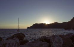 在日落的一条小船在海的山后 图库摄影