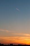 在日落的一架飞机在城市 免版税库存照片