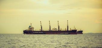 在日落的一般货物船 免版税库存图片