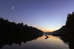 在日落的上升的新月,在河 新月形月亮明白天空 图库摄影