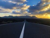在日落的不尽的路在兰萨罗特岛乡下  库存图片
