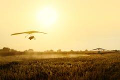 在日落的两悬挂式滑翔机拖曳 库存图片