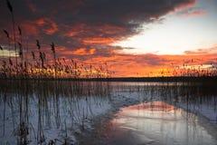 在日落的五颜六色的冻结的湖 免版税库存图片