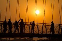 在日落的人剪影在拉克什曼Jhula桥梁 免版税图库摄影
