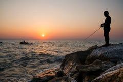 在日落的人渔 库存照片