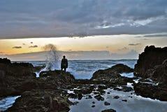 在日落的人观看的波浪崩溃 免版税库存照片