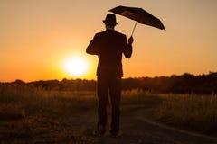 在日落的伞 免版税库存照片