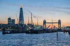 在日落的伦敦地平线与碎片和塔桥梁 图库摄影