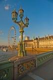 在日落的伦敦眼从威斯敏斯特桥梁 库存图片