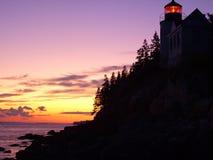 在日落的低音港口头灯塔在缅因 免版税库存图片