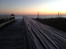 在日落的佛罗里达海滩与一个木走道 免版税库存照片
