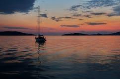 在日落的偏僻的帆船在Prvic海岛,克罗地亚附近 库存照片