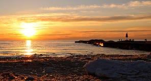 在日落的光彩的橙色和黄色颜色在休伦湖畔当冬天雪和冰融解 免版税库存照片