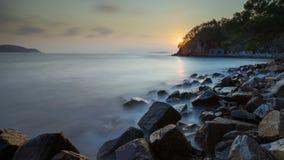 在日落的光滑的水沿海 免版税图库摄影
