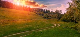 在日落的农村土路 绿草领域和山风景 免版税图库摄影