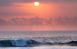 在日落的冲浪者骑马在海浪 免版税库存照片