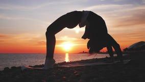 在日落的剪影年轻女人实践的瑜伽在海 人生的剪影瑜伽的愉快的片刻在海滩的在 股票视频