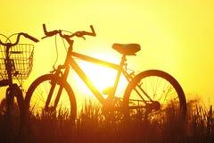 在日落的剪影自行车 免版税库存照片