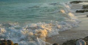 在日落的加勒比海滩与白色沙子和熔岩岩石 免版税库存照片