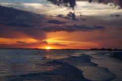 在日落的华美的橙色天空在Ft 梅尔思海滩,佛罗里达作为波浪滚动在岸上 免版税库存照片