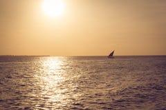 在日落的单桅三角帆船 库存图片