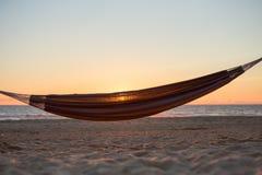 在日落的吊床在海滩 库存照片