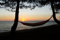 在日落的吊床在海滩 免版税库存图片