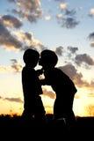 在日落的哥哥亲吻的婴孩剪影 免版税库存图片