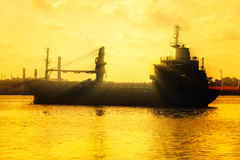 在日落的商业货船 免版税库存照片