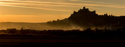 在日落的城堡和村庄剪影 免版税库存照片